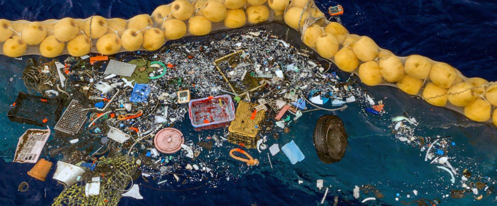 In this undated handout photo provided by The Ocean Clean Up, plastic is retained in front of an extended cork line in the Pacific Ocean. A Dutch inventor says that after a series of setbacks his system for catching plastic floating in the Pacific be