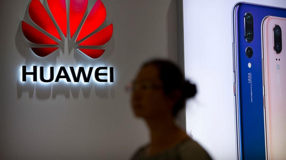 "FILE - In this July 4, 2018, file photo, a shopper walks past a Huawei store at a shopping mall in Beijing. Canada's national game _ brought to you by China's Huawei. As a feud deepens between Beijing and Ottawa over the telecom giant, the company's sponsorship of the flagship ""Hockey Night in Canada"" broadcast raised questions about its involvement in a beloved national institution. (AP Photo/Mark Schiefelbein, File)"