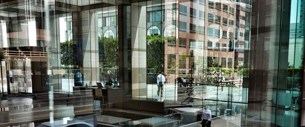FILE - In this Aug. 27, 2018, file photo downtown Los Angeles buildings and office workers are reflected in the front windows of a building. California has proposed rules for companies preparing for the state's data privacy bill, including setting ou
