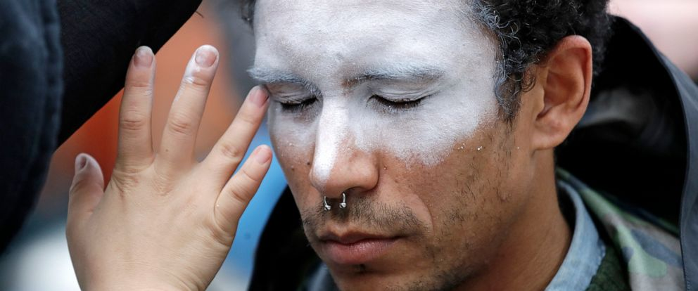 """FILE - In this Oct. 31, 2018, file photo, a man, who declined to be identified, has his face painted to represent efforts to defeat facial recognition during a protest at Amazon headquarters over the companys facial recognition system, """"Rekognition,"""