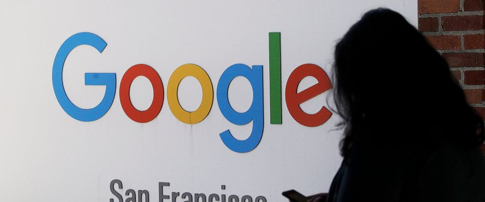 FILE - In this May 1, 2019, file photo, a person walks past a Google sign in San Francisco. Google employees are calling on the company to pledge it won't work with U.S. Customs and Border Protection or Immigration and Customs Enforcement _ the lates