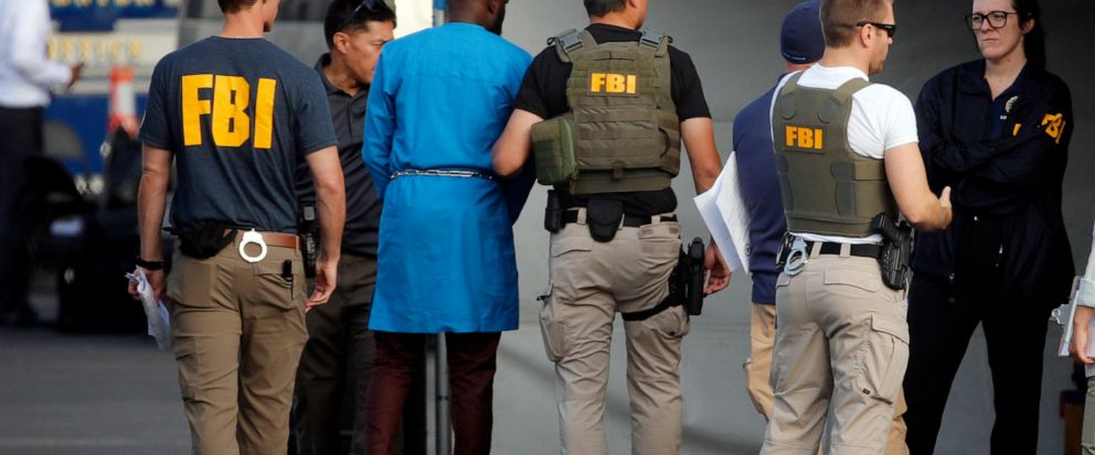 Federal agents hold a detainee, second from left, at a downtown Los Angeles parking lot after predawn raids that saw dozens of people arrested in the L.A. area Thursday, Aug. 22, 2019. U.S. authorities have unsealed a 252-count federal grand jury ind