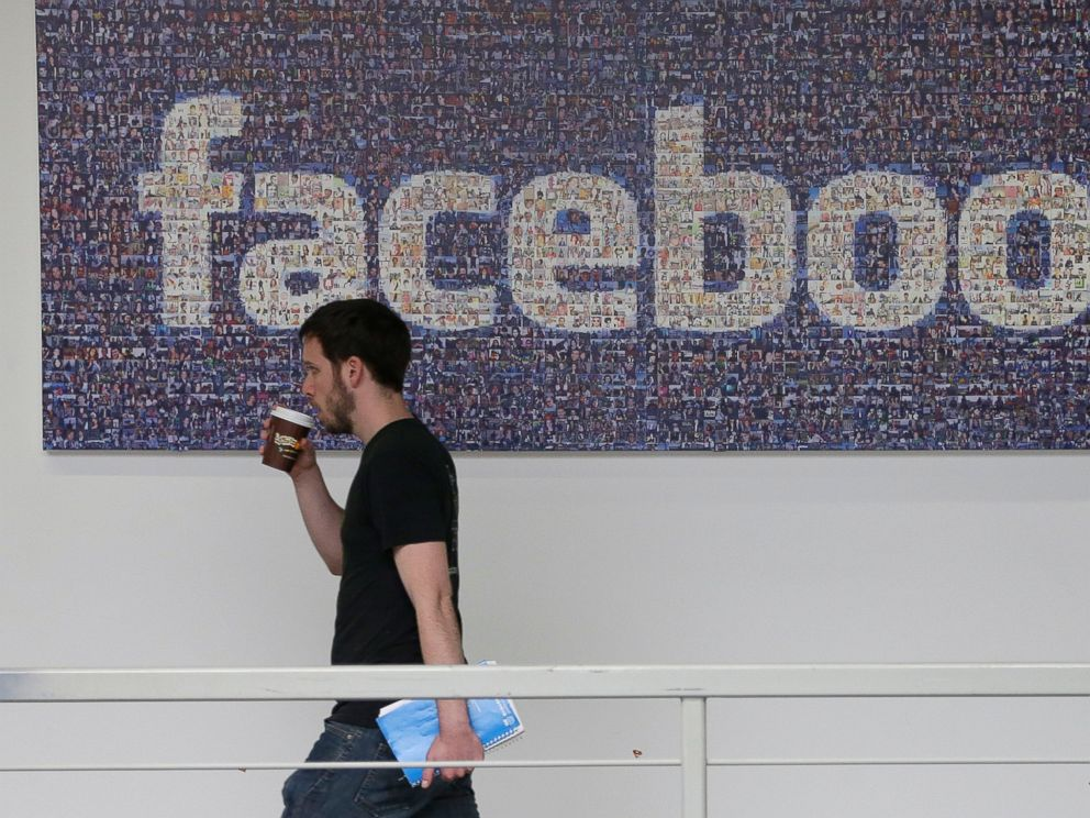PHOTO: A Facebook employee walks past a sign at Facebook headquarters in Menlo Park, Calif., March 15, 2013.