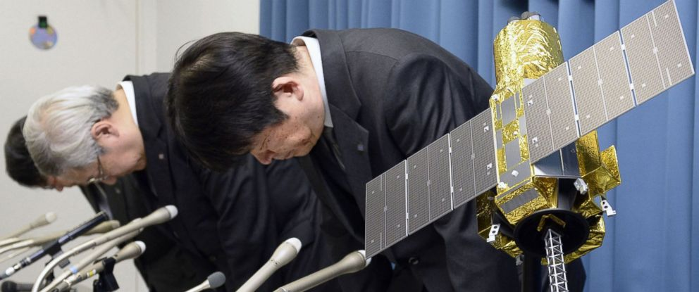 "PHOTO: Officials of the Japan Aerospace Exploration Agency bow beside the model of an X-ray astronomy satellite called ""Hitomi"" in the agency in Tokyo, Japan, April 28, 2016."