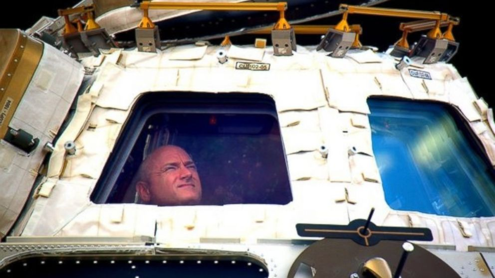 In this undated photo provided by NASA on March 1, 2016, astronaut Scott Kelly looks out the cupola of the International Space Station. Kelly closes the door Tuesday to an unprecedented year in space for NASA, flying back to the planet and loved ones he left behind last March.