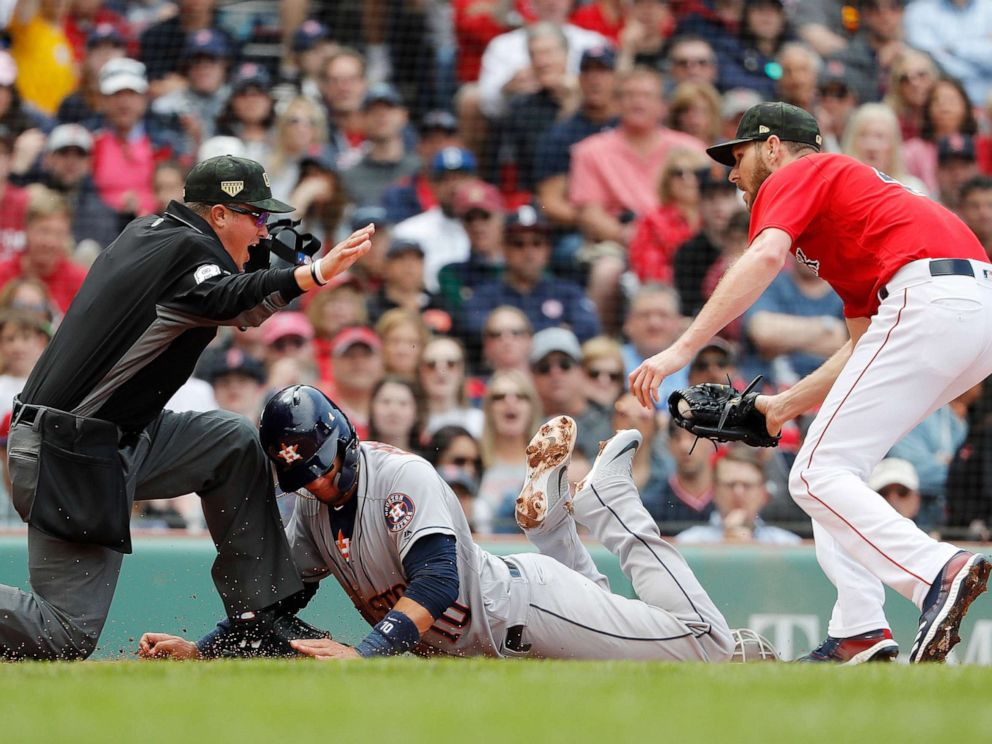 PHOTO: Houston Astros Yuli Gurriel, center, is called safe by umpire Cory Blaser, left, after scoring on a wild pitch by starting pitcher Chris Sale, right, during the second inning of a baseball game, May 19, 2019, at Fenway Park in Boston.