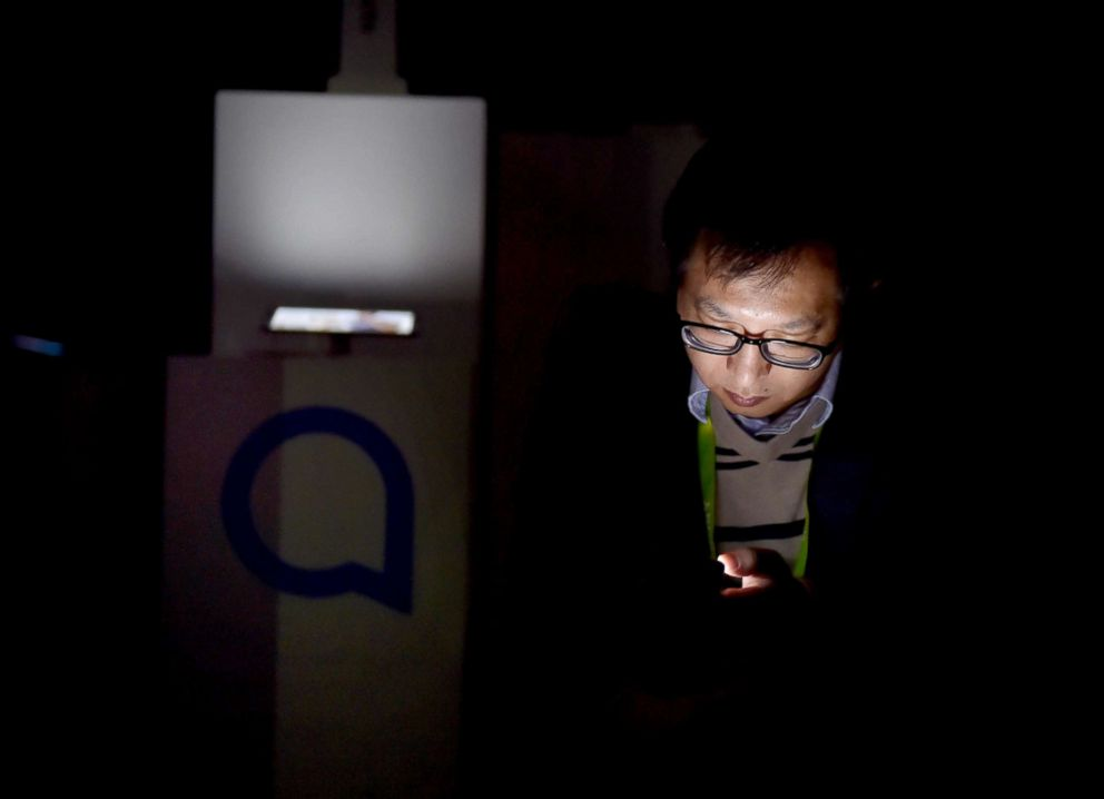 PHOTO: An attendee uses his electronic device after power was lost during CES 2018 inside the central hall at the Las Vegas Convention Center, Jan. 10, 2018, in Las Vegas.