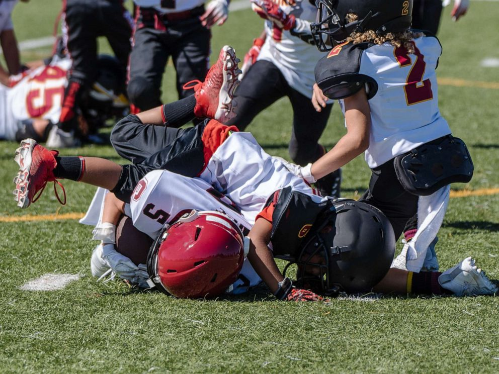 PHOTO: A youth football player is tackled and at bottom of a pile during a game.