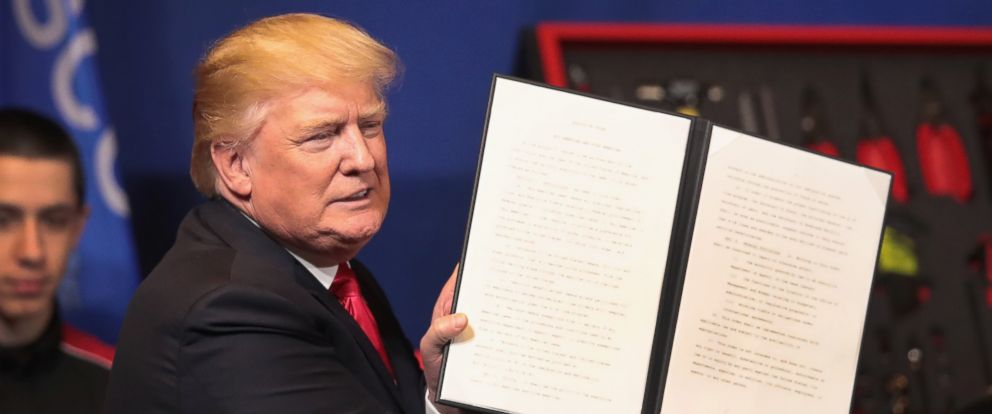 PHOTO: President Donald Trump signs an executive order to try to bring jobs back to American workers and revamp the H-1B visa guest worker program during a visit to the headquarters of tool manufacturer Snap-On, April 18, 2017, in Kenosha, Wisconsin.
