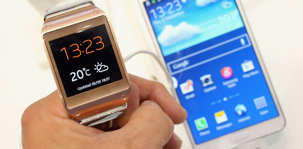 PHOTO: Galaxy Gear smartwatch is held next to the new Galaxy Note 3 smartphone