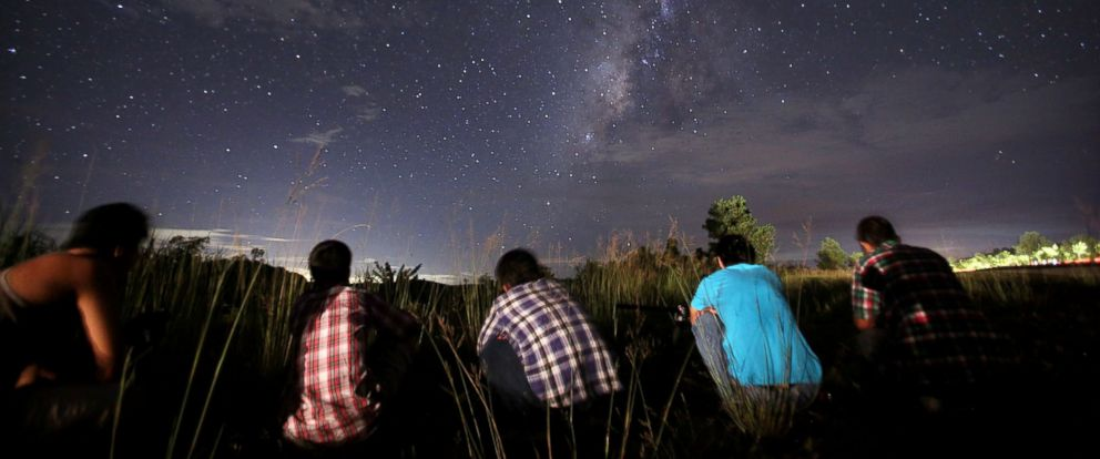 PHOTO: This long-exposure photograph taken on Aug. 12, 2013 shows people watching for the Perseid meteor shower in the night sky near Yangon.