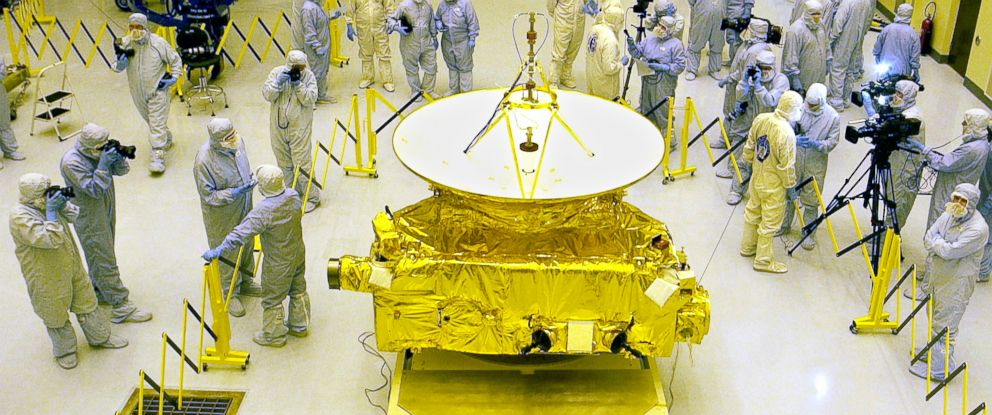PHOTO: Members of the media garbed in protective unforms view NASAs New Horizons spacecraft on Nov. 4, 2005 at Kennedy Space Center, Fla.