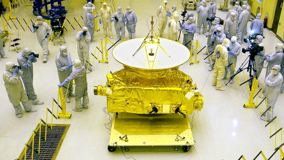Members of the media garbed in protective uniforms view NASA's New Horizons spacecraft on Nov. 4, 2005 at Kennedy Space Center in Florida.