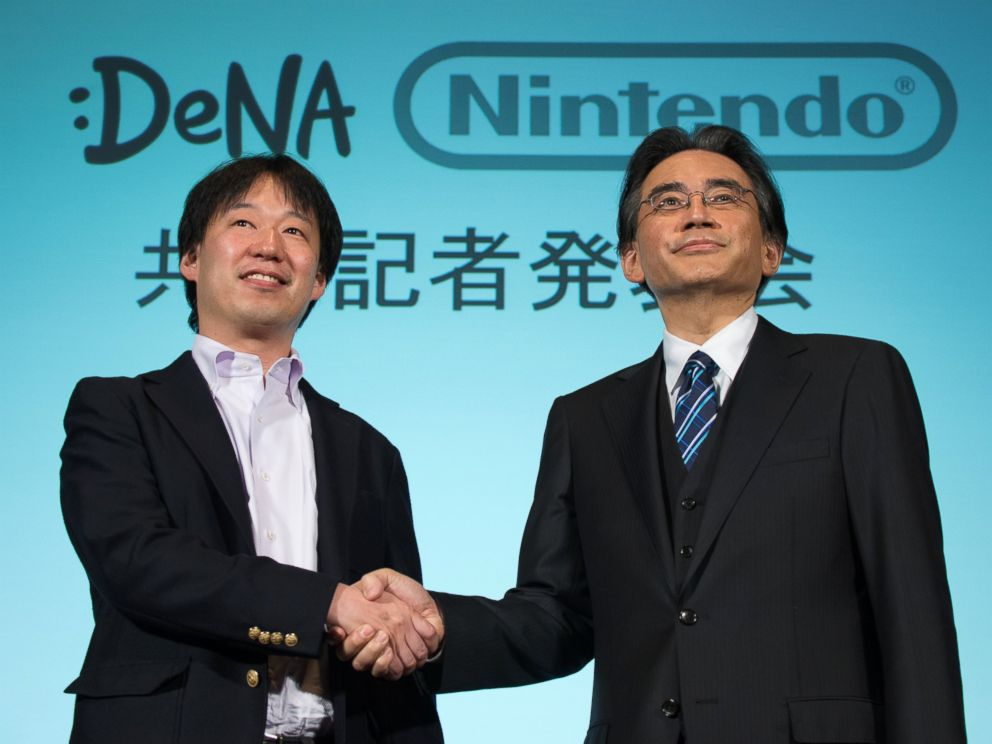 PHOTO: Satoru Iwata, president of Nintendo Co., right, and Isao Moriyasu, president and chief executive officer of DeNA Co., shake hands during a joint news conference in Tokyo, Japan, March 17, 2015.
