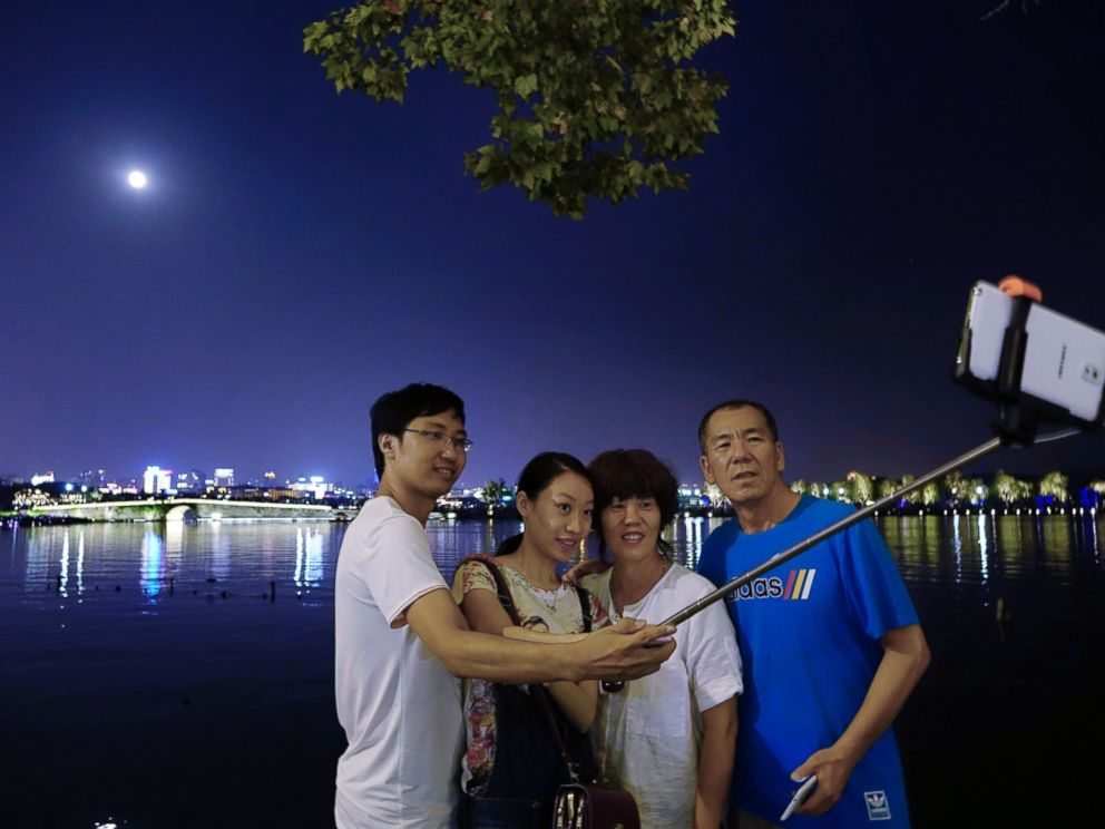 PHOTO: People take selfies with the full moon at the West Lake during the Mid-Autumn Festival, on Sept. 27, 2015 in Zaozhuang, China.
