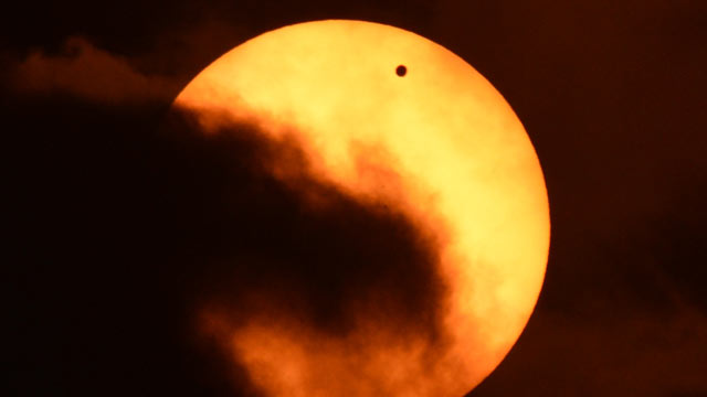 PHOTO: Clouds partially obscure the sun during the transit of Venus on June 5, 2012 as seen from Riverside Park on the west side of Manhattan in New York.