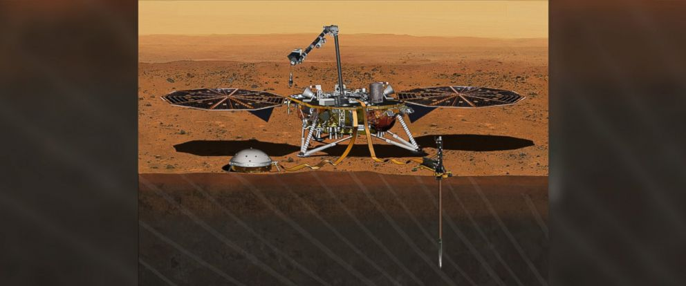 PHOTO: An artists depiction shows NASAs Insight lander on Mars after the lander has deployed a seismometer and heat probe into the ground.
