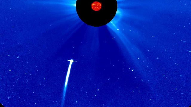 PHOTO: Comet Lovejoy plunging toward the sun, as seen by NASAs SOHO spacecraft. The image is in false color. The sun is blocked by a disc so that its light will not drown out everything around it.