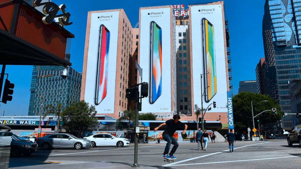A skateboarder jumps the curb crossing a street in Los Angeles on Oct. 13, 2017, where advertising for Apple's new iPhone X, due for release on November 3, covers the sides of three buildings.