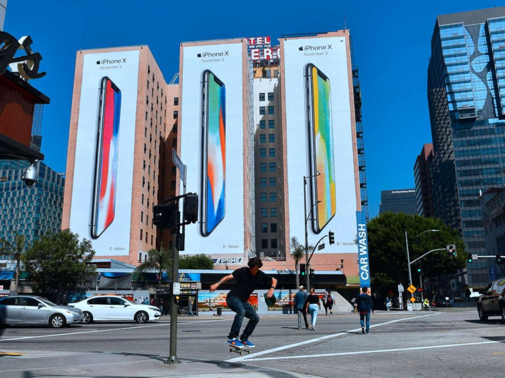 PHOTO: A skateboarder jumps the curb crossing a street in Los Angeles on Oct. 13, 2017, where advertising for Apples new iPhone X, due for release on November 3, covers the sides of three buildings.