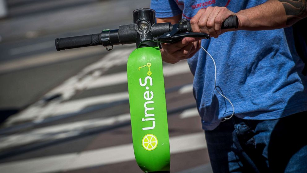 A person unlocks a Neutron Holdings Inc. LimeBike shared electric scooter on Market Street in San Francisco, April 13, 2018.