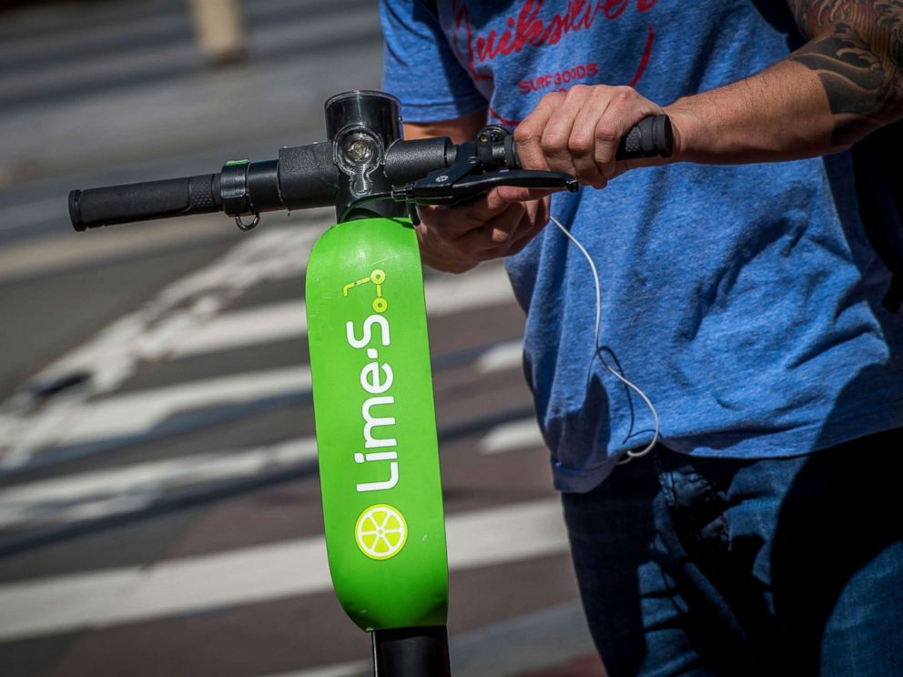 PHOTO: A person unlocks a Neutron Holdings Inc. LimeBike shared electric scooter on Market Street in San Francisco, April 13, 2018.