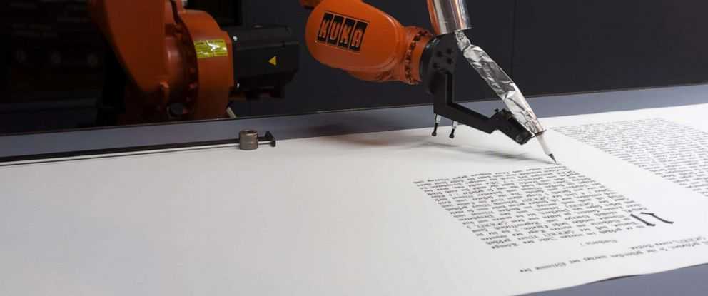 PHOTO: A one-armed robot writing the text from the Bible in Trier, Germany in 2012.