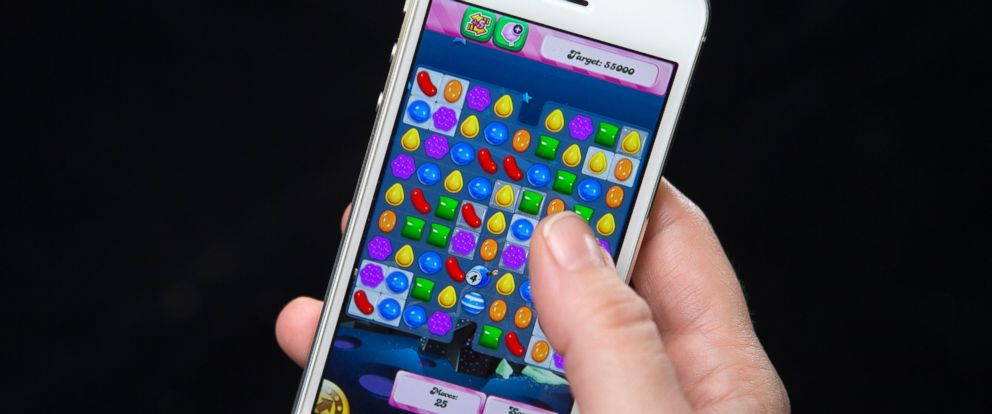 PHOTO: A woman poses for a photo illustration with an iPhone as she plays Candy Crush in New York, Feb. 18, 2014.