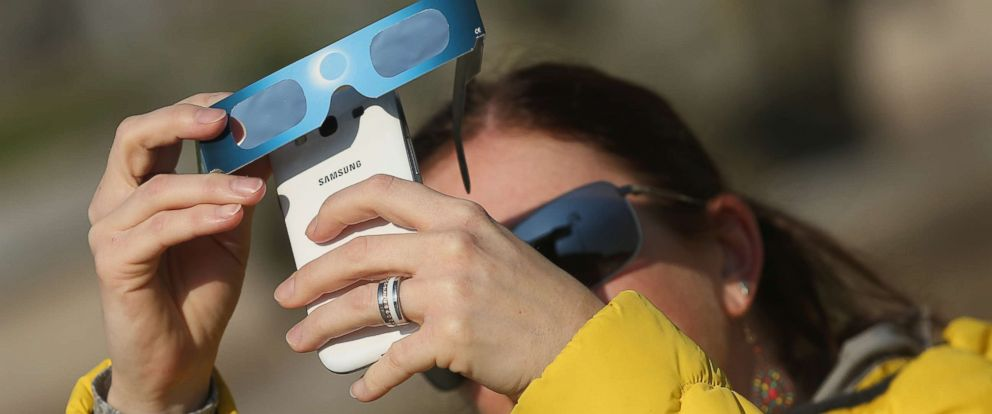 PHOTO: A woman uses special glasses and a smartphone to photograph a partial solar eclipse near the Brandenburg Gate, March 20, 2015, in Berlin.