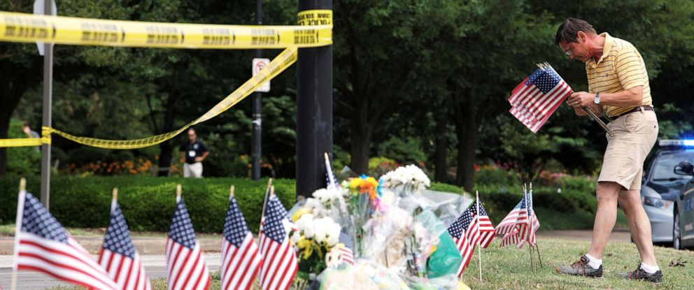 PHOTO: A man places flags at a makeshift memorial outside a municipal government building where a shooting incident occurred in Virginia Beach, Va., June 1, 2019.