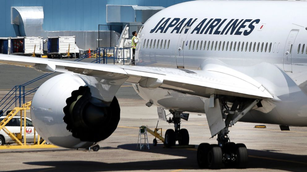 An airport worker enters a Japan Airlines Boeing 787 aircraft as it sits on the tarmac at Terminal E at Logan International Airport in Boston, July 19, 2013.
