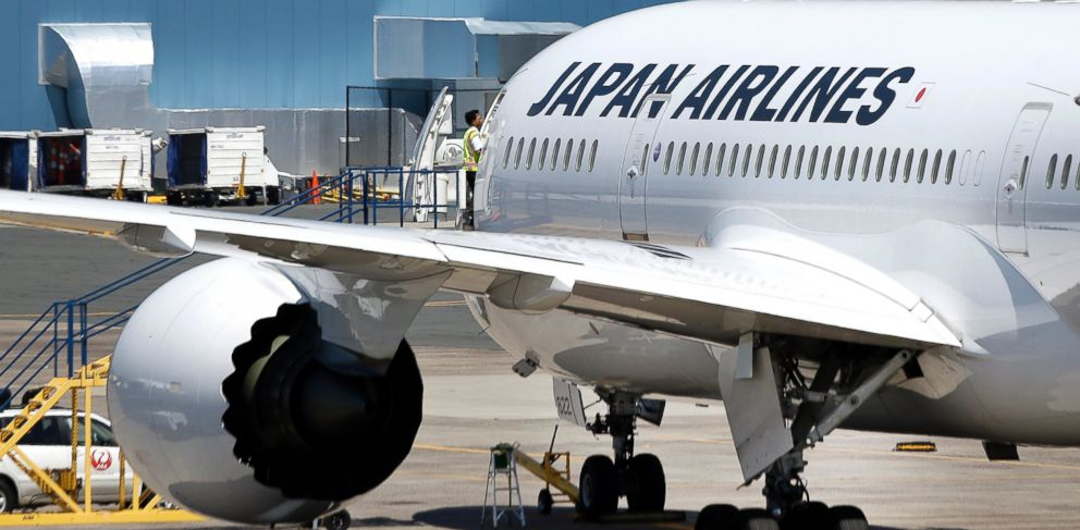 PHOTO: An airport worker enters a Japan Airlines Boeing 787 aircraft.
