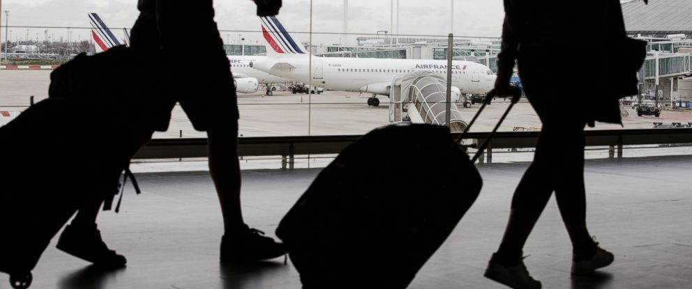 PHOTO: Passengers pull their luggage inside a terminal building as an Air France aircraft, operated by Air France-KLM Group, stand on the tarmac beyond, at Charles de Gaulle airport on Jan. 28, 2016 in Paris.