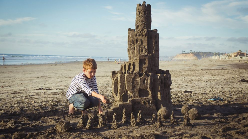 A boy puts builds a sandcastle on the beach in San Diego.