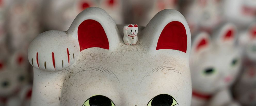 In this June 25, 2019, photo, a small beckoning cat figurine is place on top of a large statue at Gotokuji Temple in Tokyo. According to a centuries-old legend provided by the temple, Gotokuji, a Buddhist temple located in the quiet neighborhood of S