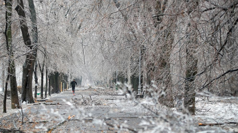 A man jogs along a path with ice covered fallen tree branches in Bucharest, Romania, Saturday, Jan. 26, 2019. Severe weather conditions has settled on much of the region with freezing rain disrupting roads and air traffic. (AP Photo/Vadim Ghirda)