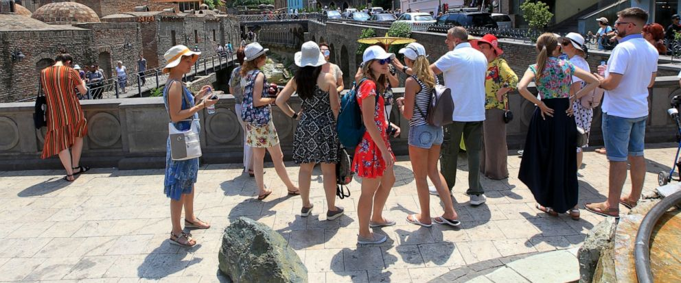 FILE - In this file photo taken on Saturday, June 22, 2019 a group of Russian tourists listen to a guide in The Old Town of Tbilisi, Georgia. The last direct flight between Russia and Georgia landed in Moscow Sunday evening July 7, 2019, putting into
