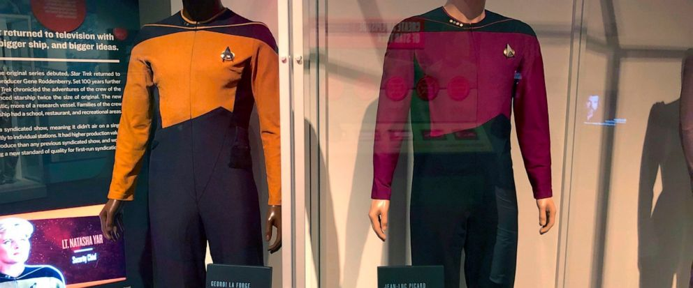 """In this May 9, 2019 photo, the actual uniforms worn by actors LaVar Burton, who played the character Geordi La Forge, and Patrick Stewart, who played the character Jean Luc Picard, are displayed at the """"Star Trek: Exploring New Worlds"""" exhibit at The"""