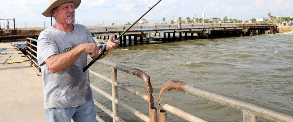 In this Monday, Sept. 9, 2019 photo, a Gerald Cross sets a line in the channel at Rollover Pass on the Bolivar Peninsula near Galveston, Texas. Cross, who has been fishing at Rollover Pass since he was 10-years old, voiced his objections about fillin