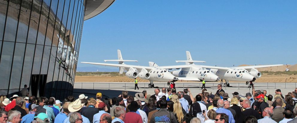 FILE - In this Oct. 17, 2011, file photo a crowd gathers outside Spaceport America for a dedication ceremony as Virgin Galactics mothership WhiteKnightTwo sits on the tarmac near Upham, N.M. British billionaire Richard Branson is taking another conc