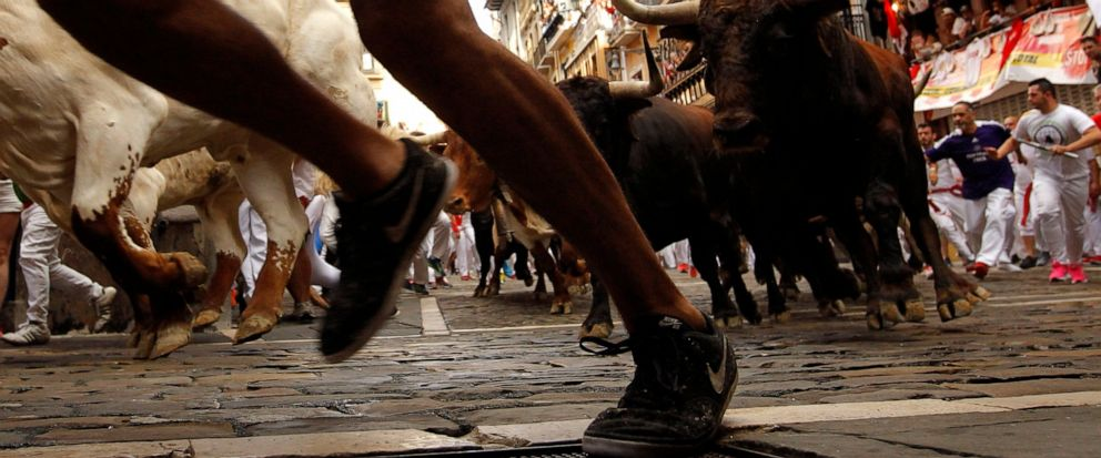 Revellers run next to fighting bulls from Cebada Gago ranch, during the running of the bulls at the San Fermin Festival, in Pamplona, northern Spain, Monday, July 8, 2019. Revellers from around the world flock to Pamplona every year to take part in t