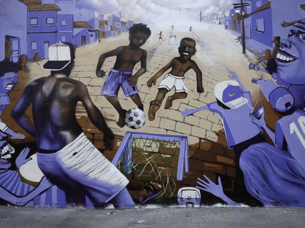 PHOTO: A wall decorated with a mural depicting children playing soccer at street in a favela stands in Rio de Janeiro, Brazil, May 27, 2014.
