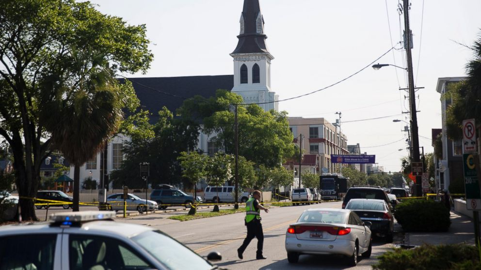 The steeple of Emanuel AME Church rises above the street as a police officer tells a car to move as the area is closed off following a shooting, June 18, 2015 in Charleston, S.C.