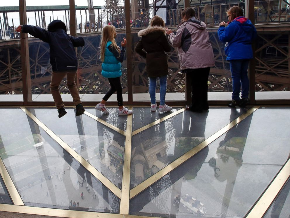 PHOTO: Visitors walk on the new glass floor at The Eiffel Tower during the inauguration of the newly refurbish first floor, in Paris, France, Oct. 6, 2014.