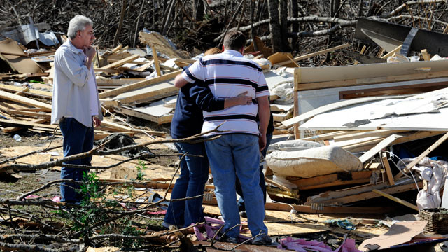 PHOTO: Relatives of Melissa Beaty console each other while looking at the home where she was killed, after a tornado touched down in Cumberland County, Tenn., Feb. 29, 2012.