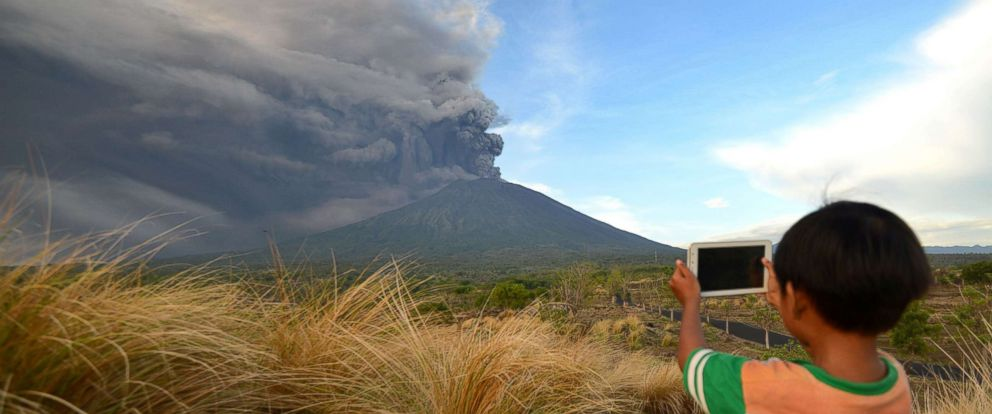 PHOTO: A boy takes pictures during Mount Agungs eruption seen from Kubu sub-district in Karangasem Regency on Indonesias resort island of Bali, Nov. 26, 2017.
