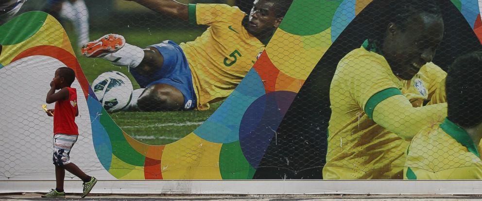 PHOTO: A boy walks past a wall in front of a mural outside the FIFA Fan Fest on Copacabana Beach on June 1, 2014 in Rio de Janeiro, Brazil.