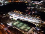 PHOTO: Crippled cruise ship, Carnival Triumph, moves into port guided by tug boats on Feb. 14, 2013 in Mobile, Ala.