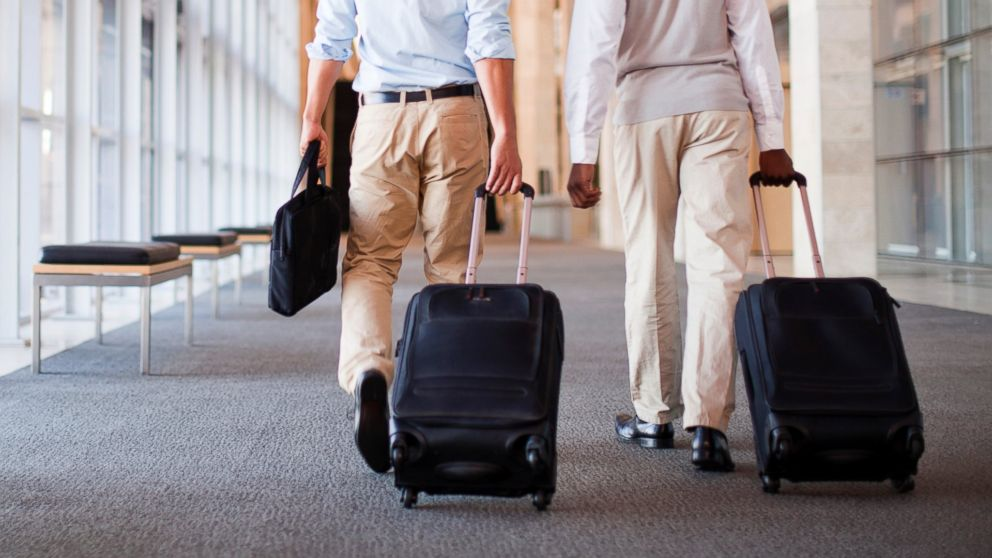 Businessmen roll luggage in hallway in this undated stock image.