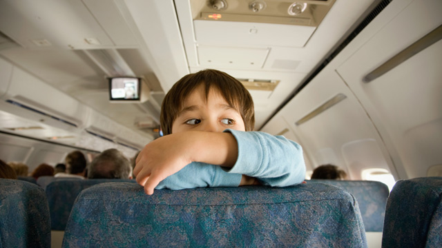PHOTO: Child climbing and looking over back of airplane seat